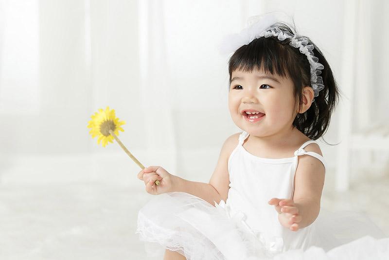1歳誕生記念女児 ガーベラを手に持つ