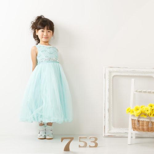 女の子水色ドレスで前進正面白壁前
